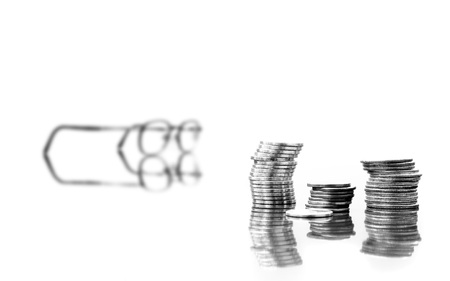 Several stacks of coins isolated on white background with reflections Imagens