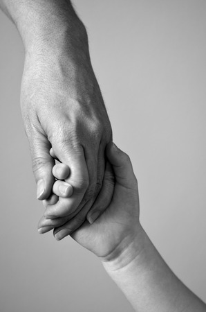 hand: Adult or parent holding the hand of a small child