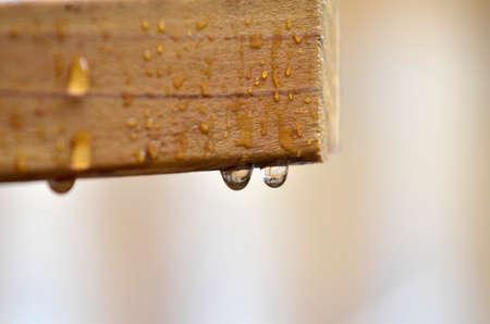 hard rain: Detail closeup of water drops on a wood railing Stock Photo