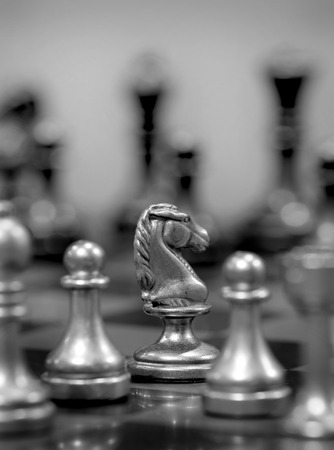 Chess board with white knight facing opponent in match photo