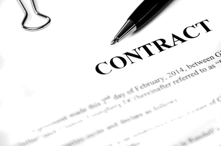obligated: Contract on desk with black pen waiting to be signed