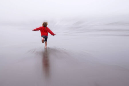 zoomed: Young girl running on beach looking at ocean zoomed blur
