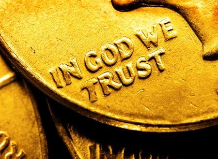 Pile of gold coins and bullion with dark background and words In God We Trust Foto de archivo