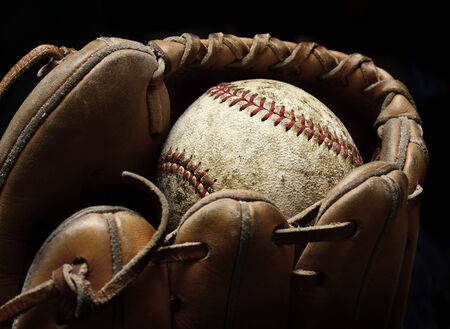 homeplate: Worn old baseball in brown leather mitt or glove