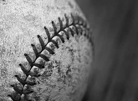 homeplate: Worn old baseball with detail of stitching