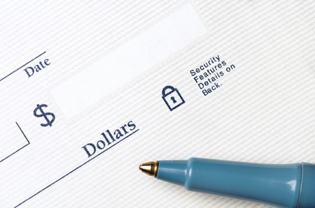 blank check: Pen on blank check to be written with dollars