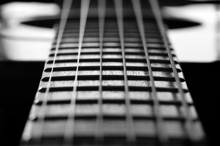 making music: Closeup detail of steel guitar strings and frets for making music