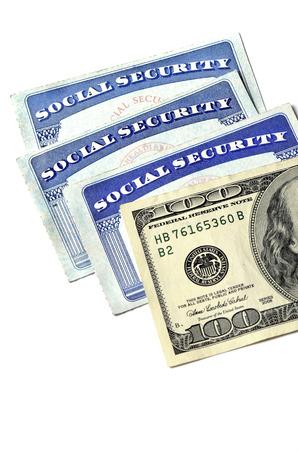 seguridad social: Detalle de varias tarjetas de Seguro Social y el dinero en efectivo que simboliza las pensiones de jubilación de seguridad financiera