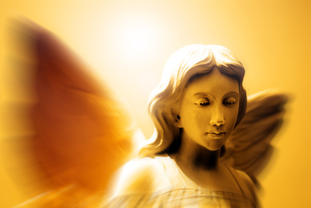 Angel with wings in front of heavenly light photo