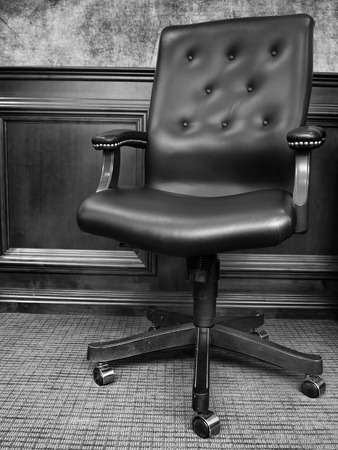 Black chair in business office with textured wall photo