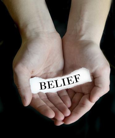 Person hands holding cupping paper message for Belief
