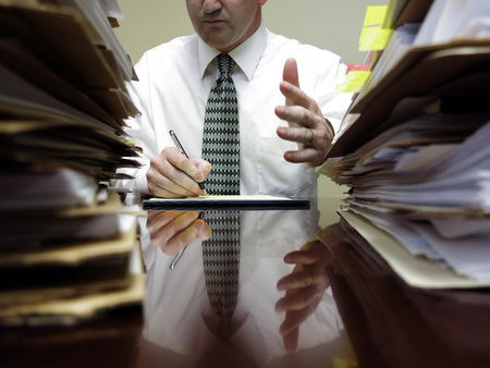 Businessman sitting at desk with pad of paper and piles files gesturing hands photo