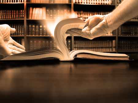 Hands turning pages in old book with library in background photo