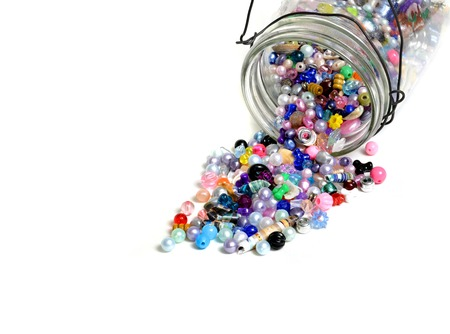 Detail of glass jar of beads on white background for crafts jewelry