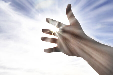 upward struggle: Persons hand reaching in hope towards heaven with sunlight shining through