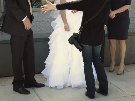 Bride and groom standing together with flowers on wedding day photographer directing for photographs Stock Photo