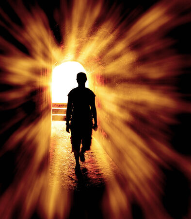 Person in long tunnel walking towards the end with light rays of hope