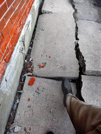壊れて危険なひびの入った歩道の上を歩く男