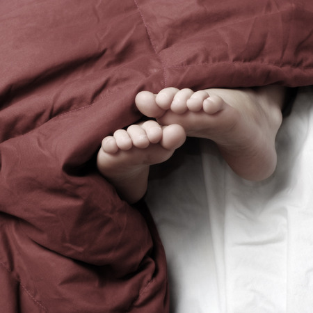 bare feet: Person sleeping with feet poking out of red blankets on bed