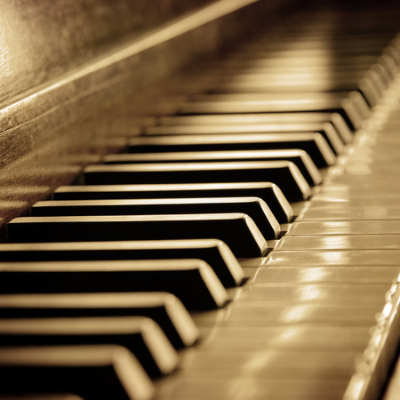 acoustically: Closeup of black and white piano keys and wood grain with sepia tone Stock Photo