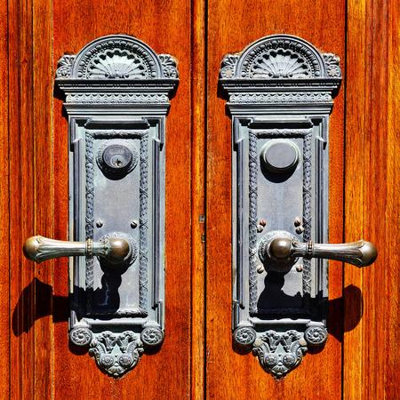 Old iron door handles on worn wooden doors