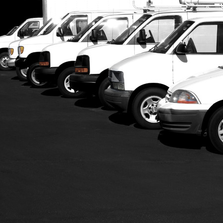 Several cars vans and trucks parked in parking lot for sale photo
