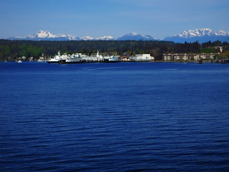 View of by or harbor in pacific northwest with mountains in background photo
