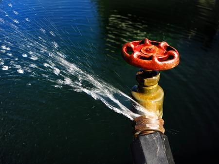 llave de agua: Detalle de la conexión de grifo de la manguera con fugas y chorros de agua pulverizada