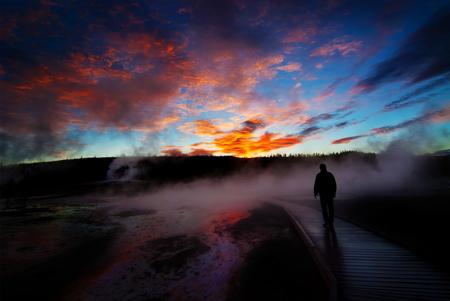 geysers: Sunrise near Yellowstone geysers with steam and silhouette of person on boardwalk
