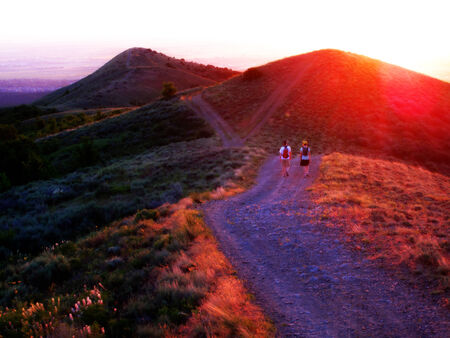 healthy path: Two girls hiking on mountains at sunset with evening glow