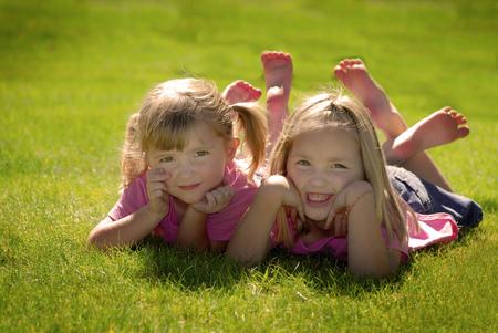 Twee zusters in roze shirts rusten hun hoofd op hun handen in het park Stockfoto