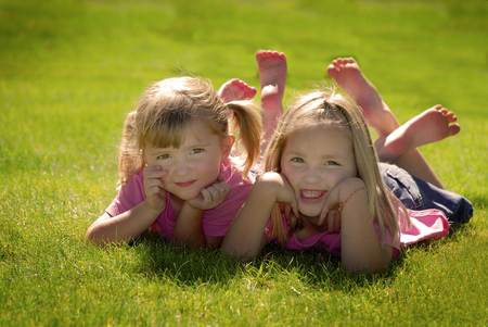 Two sisters in pink shirts resting their heads on their hands at the park Stock Photo