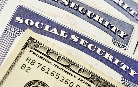 residents: Closeup detail of several Social Security Cards and cash representing finances and retirement