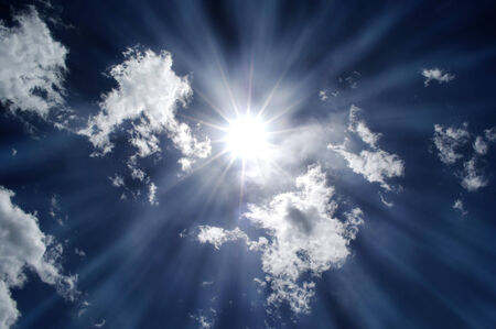 Blazing hot sun shining in blue sky with clouds Stock Photo - 30575622