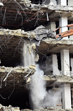 Building collapsing or being demolished with debris falling down Stock Photo