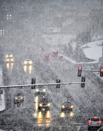 winter road: Snowy winter road with several cars driving on roadway with traffic lights