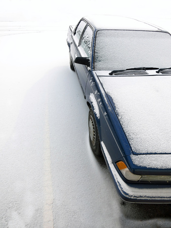 Detail of car in parking lot covered in fresh snow during winter storm photo