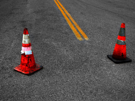 single lane road: Detail of Construction Cones and yellow street lines suggesting repair