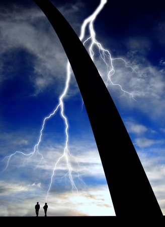Base of St. Louis Arch with Silhouette of two people and lightning photo