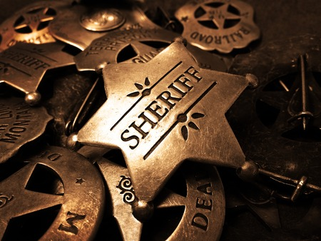 Sheriffs tin badge in pile of star law enforcement badges