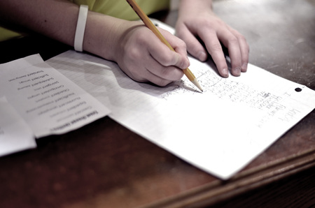 writing book: Child kid holding pencil doing home work on table bench