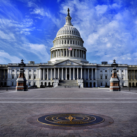 us government: United State Capitol Building for congress with american flag flowing in breeze and columns in background Stock Photo