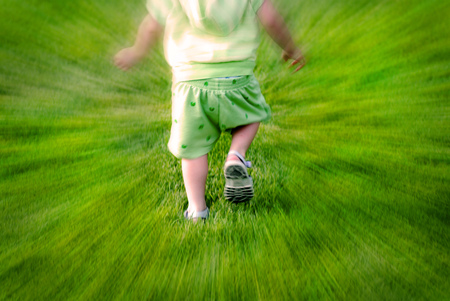 zoomed in: Zoomed shot of little child toddler running in grass having fun