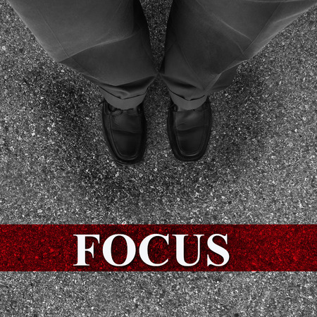 Businessman standing on asphalt starting line with motivation word of Focus photo