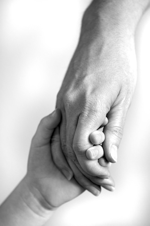 Adult or parent holding the hand of a small child photo