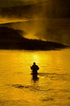 Man fishing in river with fly rod and waders photo