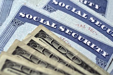 cash money: Detalle de Tarjetas de Seguro Social y varias pensiones de jubilaci�n de dinero en efectivo que simbolizan la seguridad financiera Foto de archivo