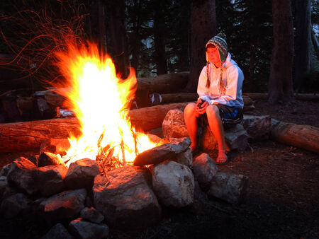 Woman looking at campfire while camping alone photo