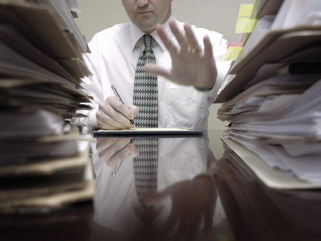 Businessman sitting at desk with pad of paper and piles files holding up hand photo