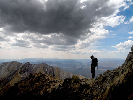 Girl hiker summit mountain top in triumph